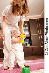 First steps - Young mother is helping her daughter to make...