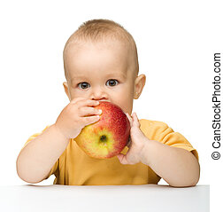 Little child is biting red apple