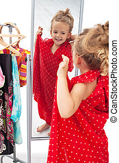 Happy little girl trying on dresses in front of mirror -...