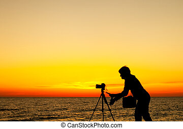 Photographer working at sunset