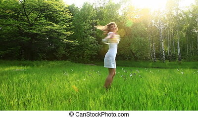 Beautiful woman spinning in grass