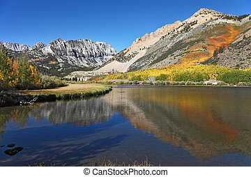 Grandiose multi-colour autumn on Northern lake. The USA