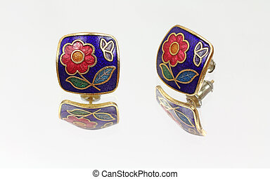 Floral pattern earrings on mirrored surface - A pair of...