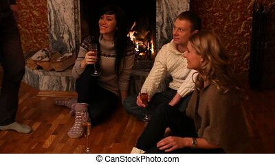 Friends at fireplace - Group of friends with flutes sitting...