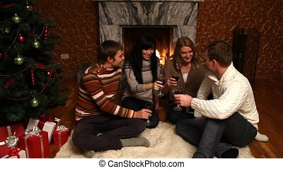 Christmas meeting - Two young couples sitting by fireplace...