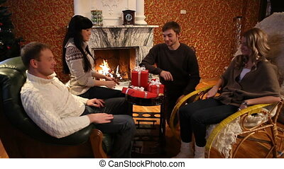 Christmas gifts - Four young people sitting at a fireplace...