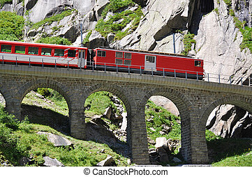 Alpine express passing bridge at St. Gotthard Pass in...