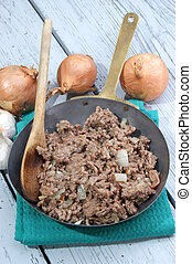fried ground beef in a rustic brass pan