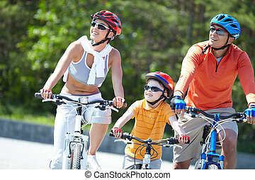Riding on bicycles - Portrait of happy family riding on...