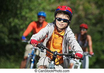 Boy riding bicycle - Portrait of happy boy riding bicycle in...