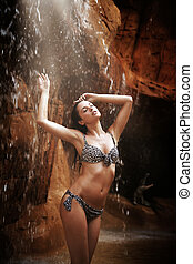 Sexy brunette enjoying jungle waterfall