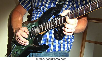 playing at electric guitar - man playing at electric guitar
