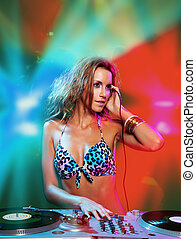 sexy blonde dj girl in the club with red and blue ligh from...