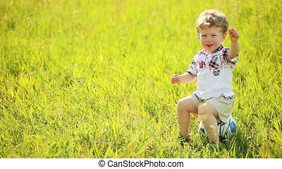 Boy sits in a field on the ball.