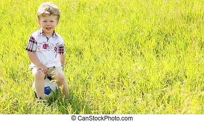 Boy sits in on the ball Look at ca - Children outdoors