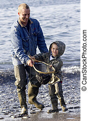 CHERISHED JOYS - Father and son, grinning with excitement,...