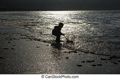 Silhouette -- Day Closes - Boy works to scoop small,...