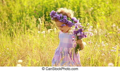 Small girl in the grass with flower