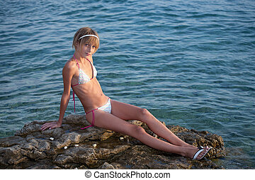Teenage girl in bikini sitting on a rock in the sea