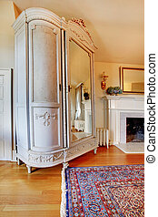 White large antique closet near fireplace