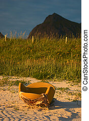 Old abandoned yellow armchair with seaview on a sandy beach close to Ramberg, Lofoten, Norway lit be the yellow midnight sun (Selective Focus, Focus on the armchair)