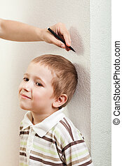 Measuring child growth - Human hand measure little child boy...