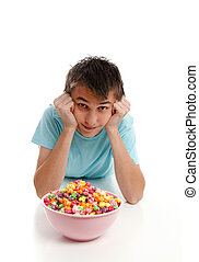 Boy relaxes with bowl of snack food
