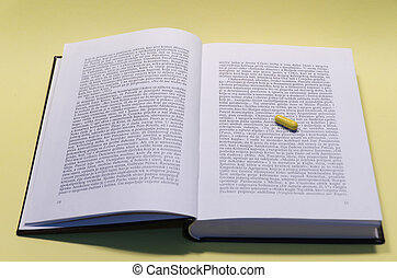 yellow sleeping capsule on a book - text, book, capusle,...