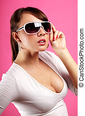 Young woman wearing sunglasses on a pink background