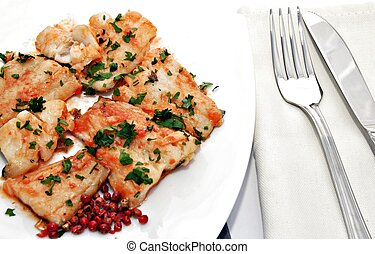 Cod dish with bits of parsley on top and red peppercorns on...
