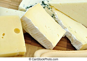 Cheeses of different types next to each other on wood