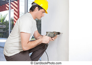 Man with electronic drill machine