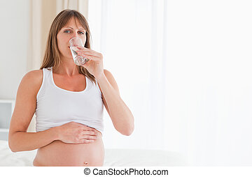 Cute pregnant female taking a pill while sitting on a bed
