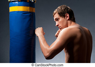 bare-chested man training with punching bag