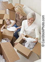Female Generations of Family Unpacking Boxes Moving House -...