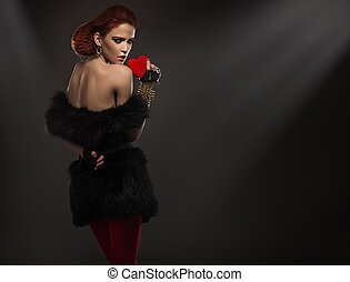 Beauty lady in fur holding red heart
