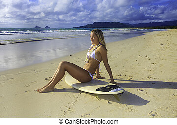 teenage girl in white bikini and flower lei with her...