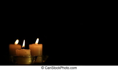 Three candles against the dark