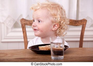 Young Boy Eating Lunch - A young boy at the lunch table,...