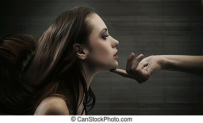 Conceptual image of a hand holding a womans head