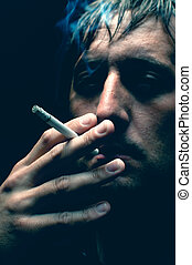 Smoker - Man smoking cigarette over black background, low...