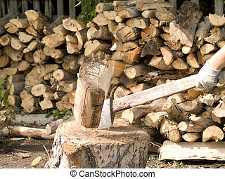 Firewood - man chopping firewood at background firewood