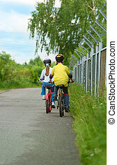 Walk on bicycles - young boy and young girl on bike