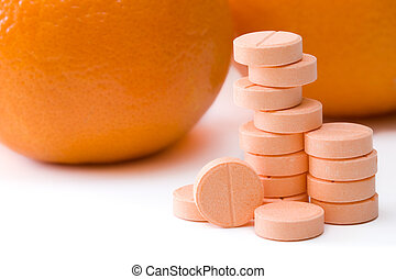Vitamin C - Pills of vitamin C on a background of orange