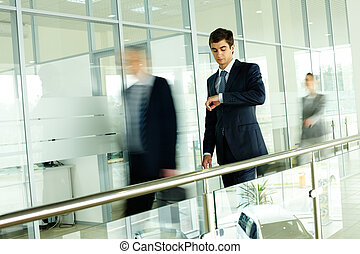 Office life - Businessman looking at watch with walking...