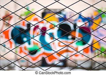 abstract graffiti through metal bars fence - view to...