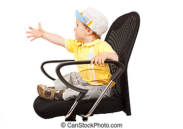 Little boy sitting on a chair reaching for something