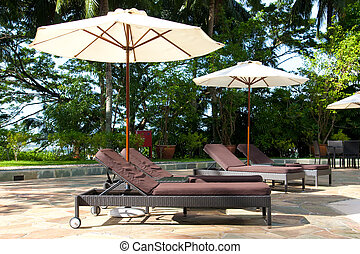 Resort swimming pool side - Recliner chairs and canopy at...