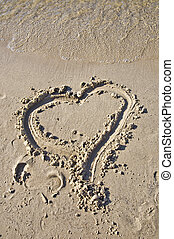 Sign of the heart in the sand Tidal wave comes to the beach...