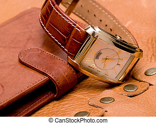 Purse - gold watch lying on a leather purse